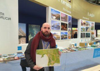 O teniente de alcalde de Cabanas Iago Varela, amosa o novo material turístico do concello en FITUR.