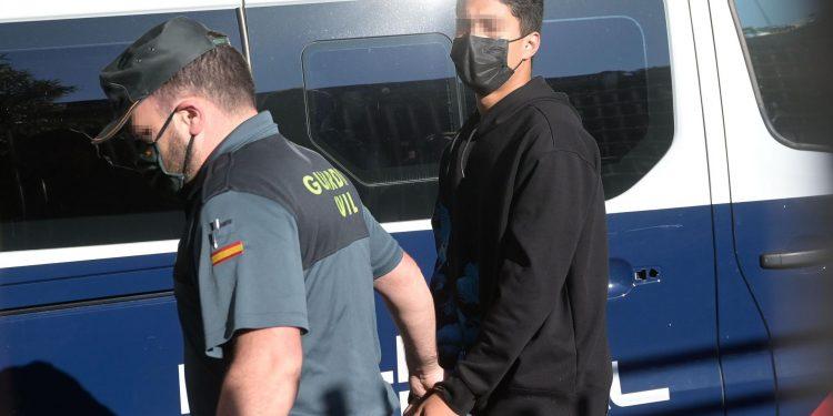 Uno de los investigados por la muerte de Samuel Luiz, esposado y acompañado de un agente de la Policía Nacional, a su entrada al Juzgado de Instrucción número 8 de A Coruña | EP