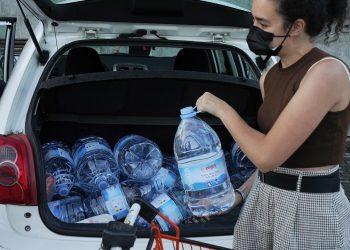 Una mujer carga con varios bidones con agua en Santiago   ÁLVARO BALLESTEROS