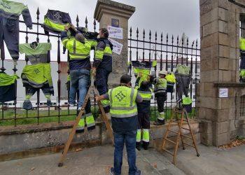 Ogperarios de ElectroRayma colgando su ropa de trabajo de la verja de Navantia Ferrol. | EUROPA PRESS